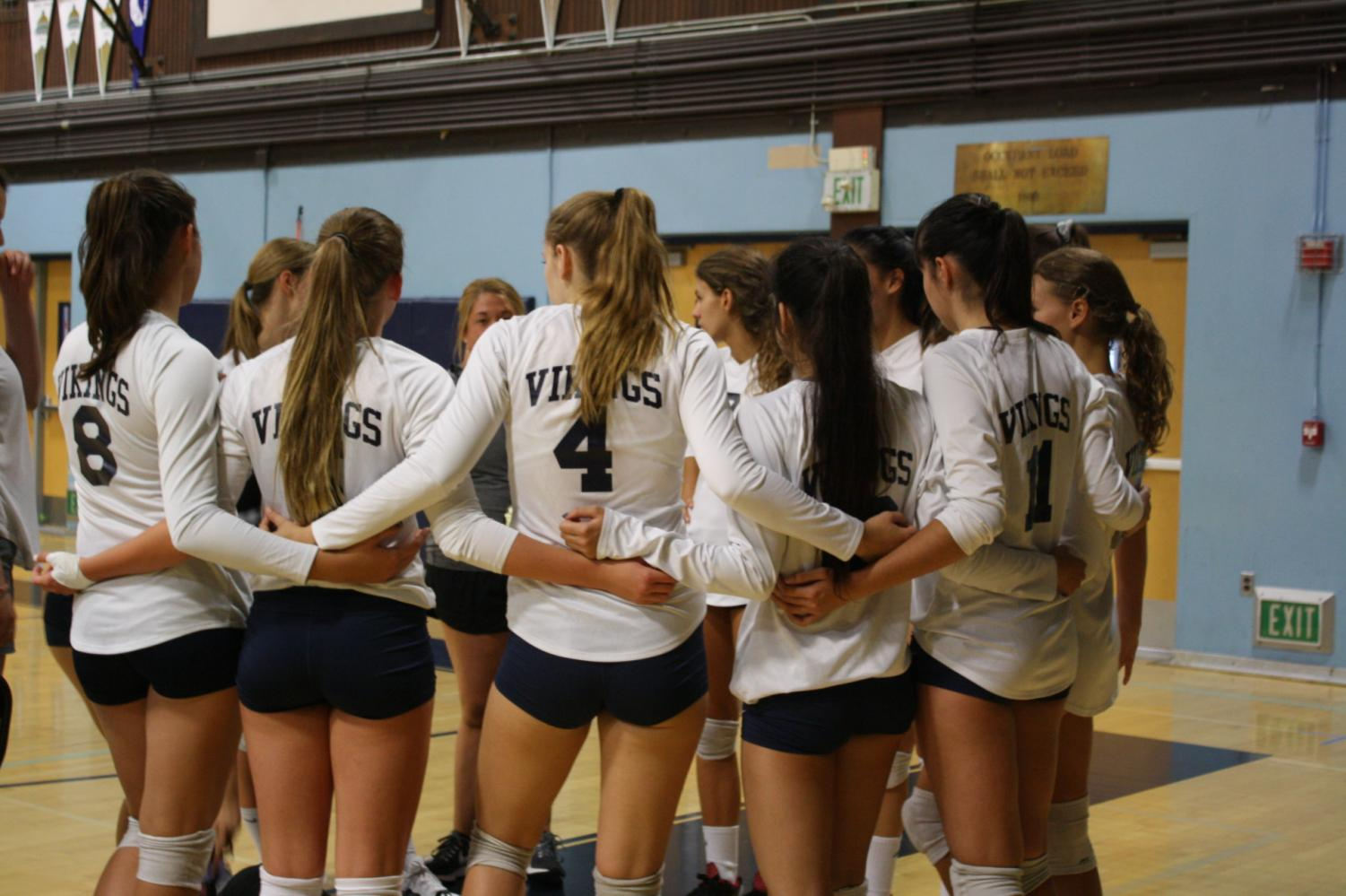 Oakmont girls volleyball team huddling together to plan their next play