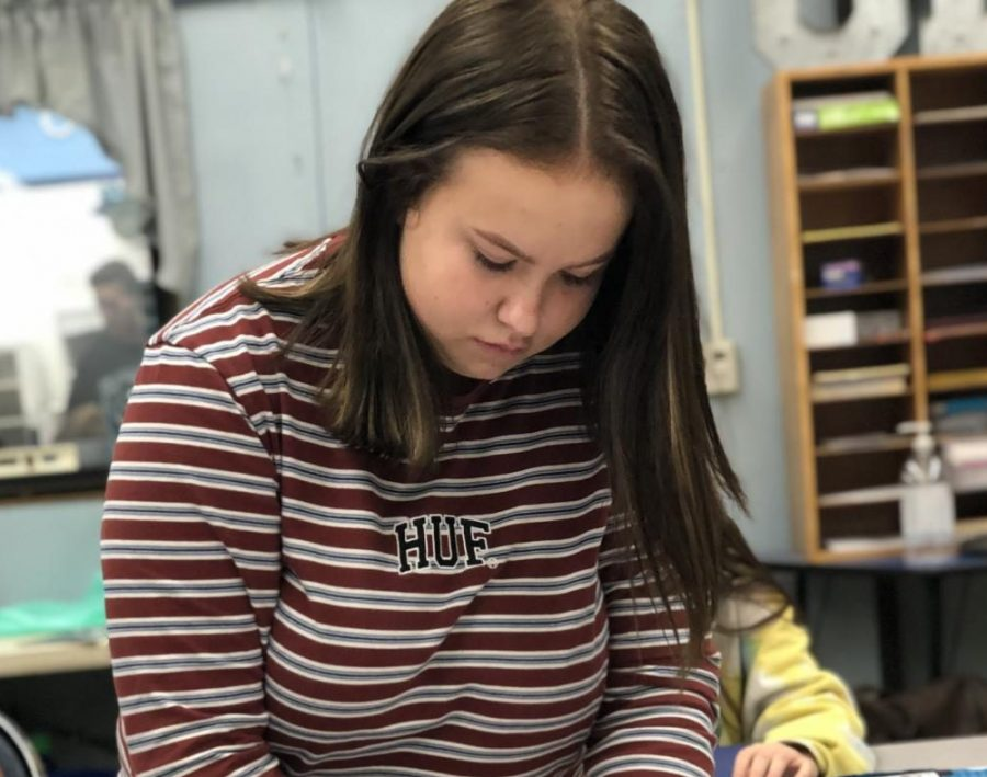 Senior Emmie Pierce wraps presents for the F.C. Joyce Elementary School