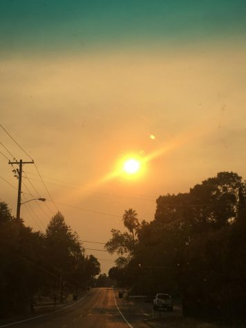 The smoke from nearby wildfires has filled the sky, causing the sun to be crimson red.