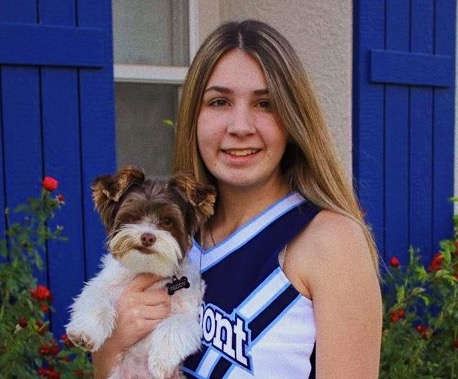 Senior Izzy Perez posing with her dog Teddy in her new cheer uniform.