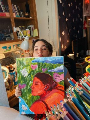 Emma Boyle posing with a painting she's done for her recent exhibition.