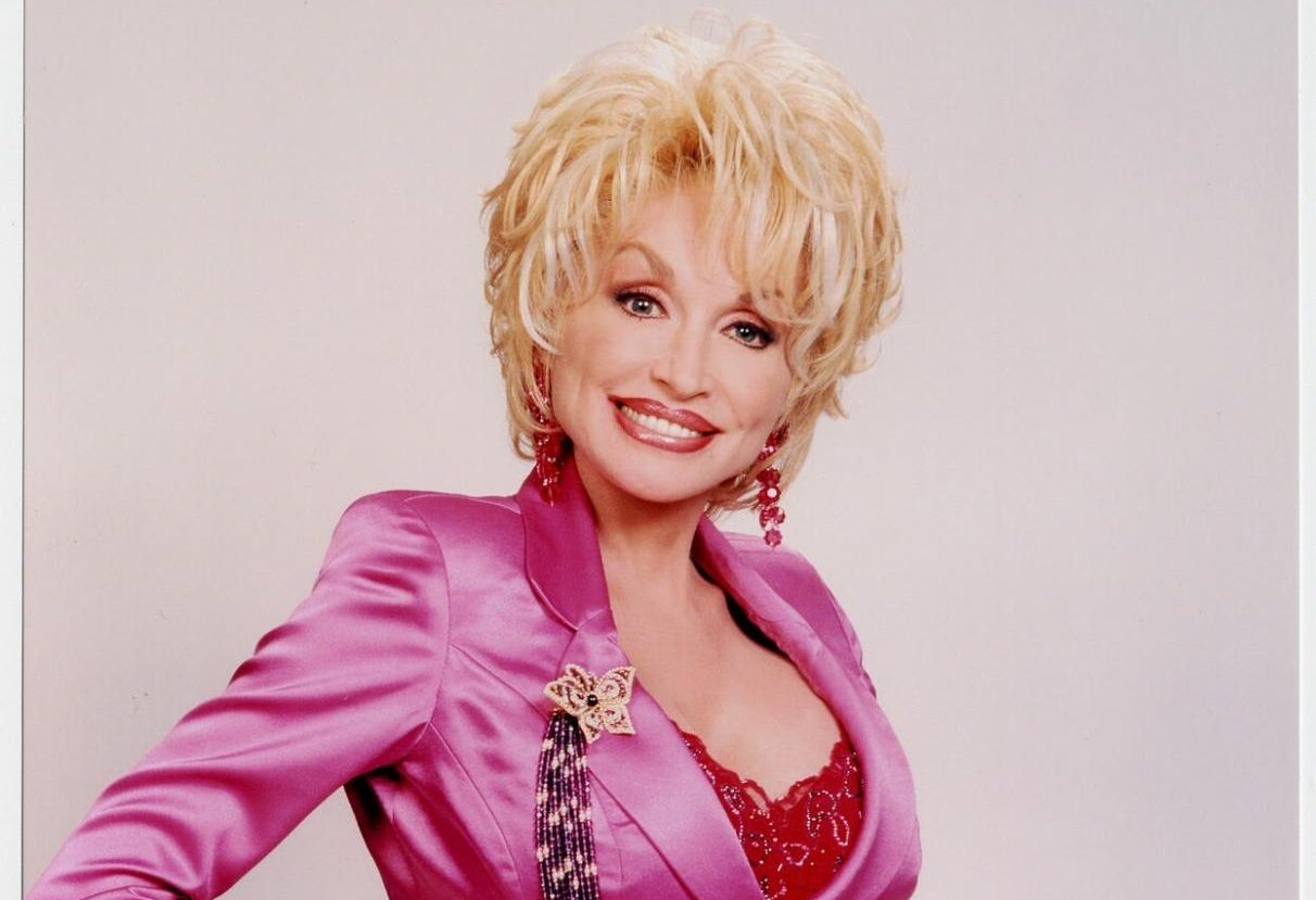 Dolly Parton in a fuchsia suit with red lace details.