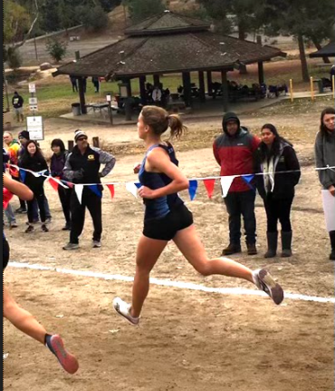 Junior Mia Hirsch running in a cross-country meet last season