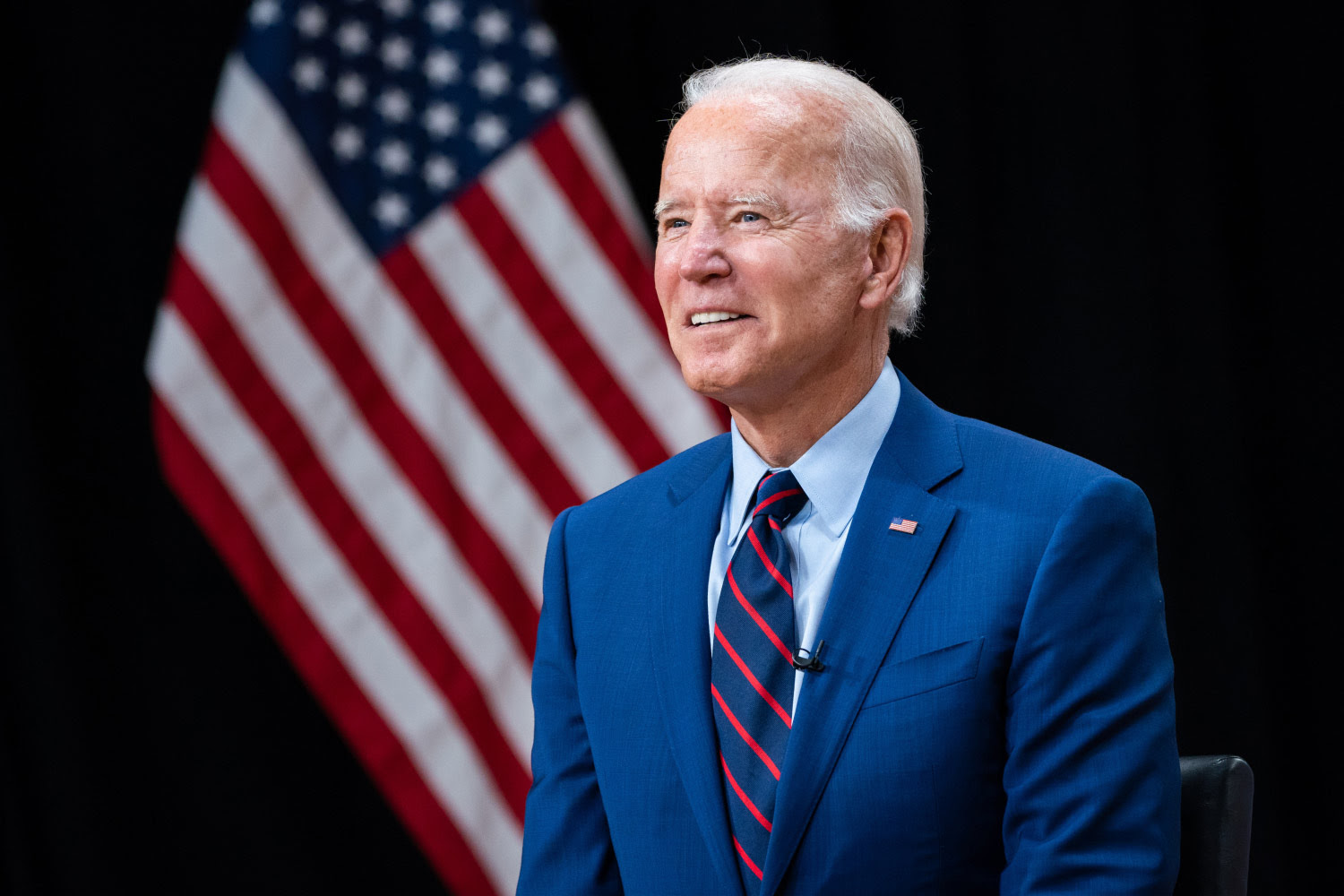 President Joe Biden standing near the American Flag, pondering what he is going to do next.