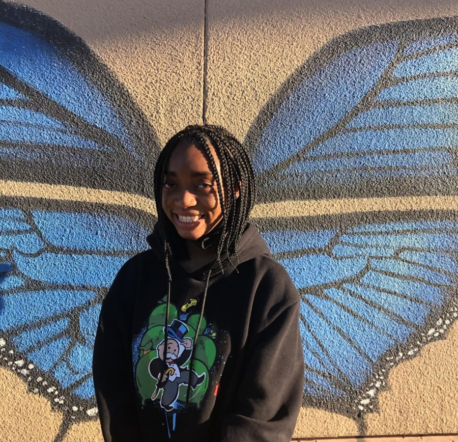 Ramyah Carter smiling bright in front of the art building.